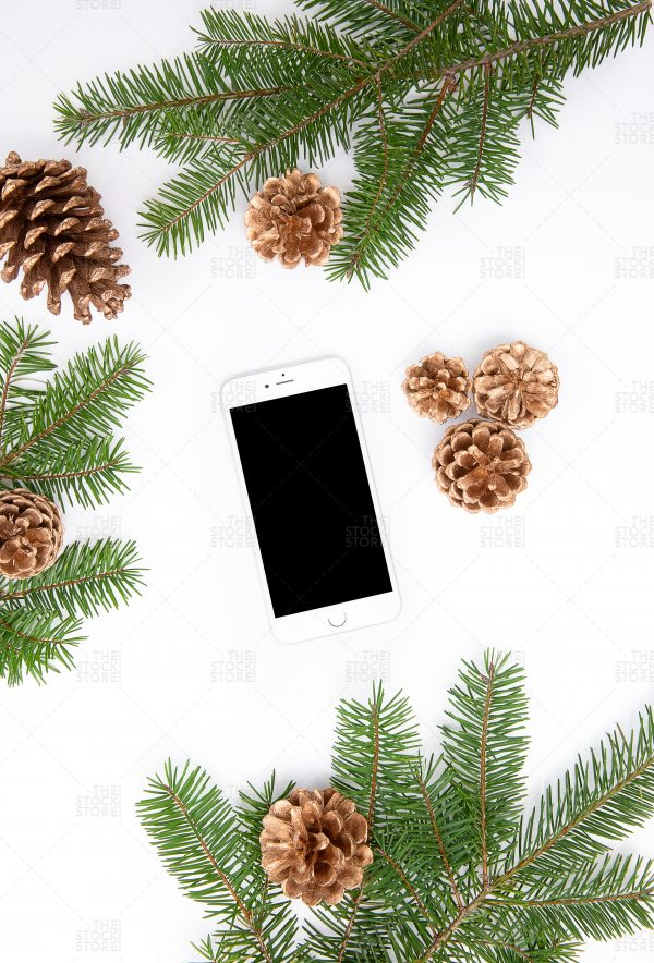Photo of iPhone with pine branches an gold pinecones