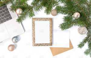 photo of laptop with a gold frame and pine branches