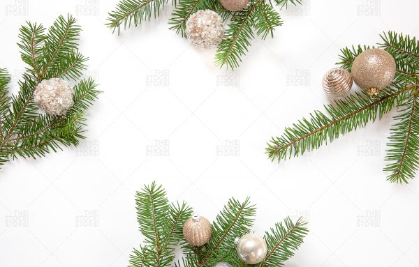 Pine branches with gold ornaments on white background